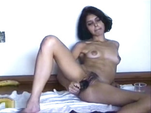 Tanned dark haired girl plays with her trimmed pussy