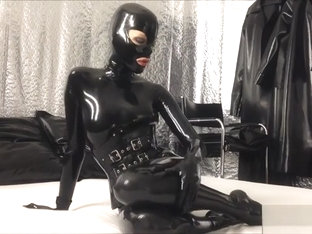 Rubberdoll in black latex enclosure - warm-up before kinky session
