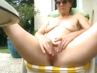 Mature honey with big tits plays with her pussy outdoors on the patio